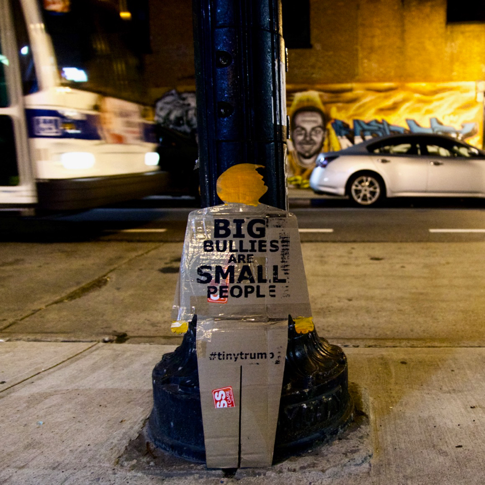 tiny trump on a sidewalk at night with the slogan 'Big Bullies Are Small People'