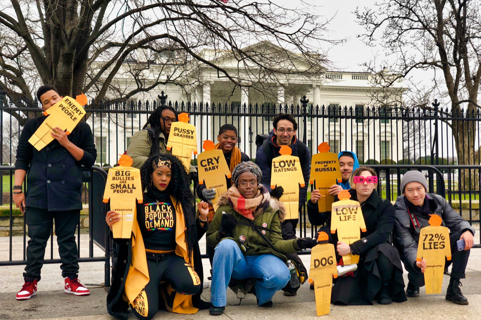 12 project participants standing in front of the White House holding tiny trumps