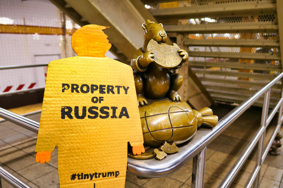tiny trump with the stamp 'Property of Russia' in the 14th street subway station next to Tom Otterness sculpture of a moneybag
