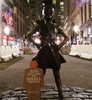 tiny trump with the stamp 'Big Bullies Are Small People' with fearless girl on Wall Street