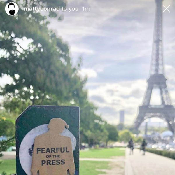 tiny trump with a stamp that says Freedom of the Press with the Eiffel Tower in the background