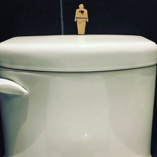 tiny trump on top of a toilet
