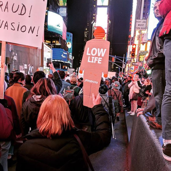 'Low Life' tiny trump being used as a protest sign in New York City's Times Square