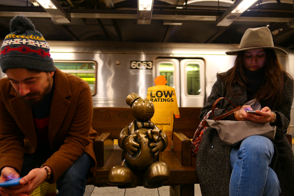 'Low Ratings' tiny trump on a nyc subway bench in between two straphangers