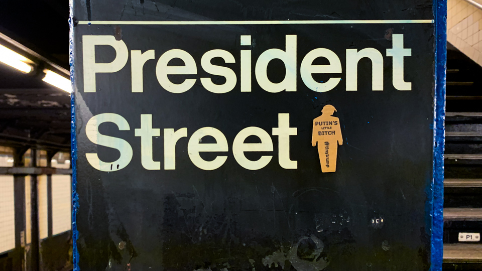 'Putins Little Bitch' tiny trump on a NYC subway sign titled 'President Street'