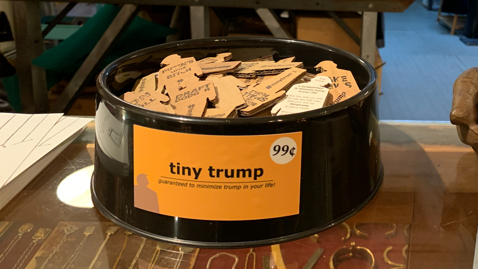 dozens of tiny trumps in a dog bowl for sale in a store (detail)